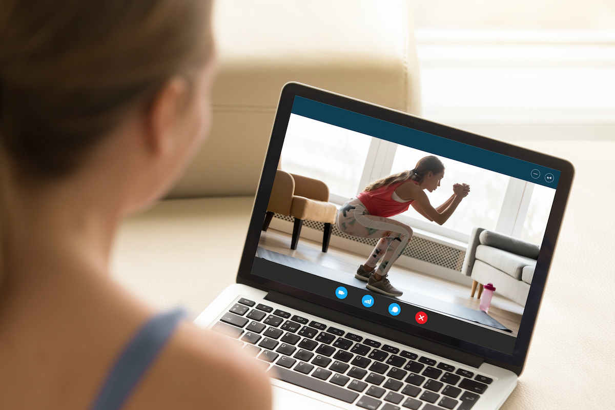 Focus on laptop screen with young woman in sportswear doing morning exercises, deep squats on yoga mat, staying fit at home. Interested girl watching online educational fitness workshop training. on laptop screen with young woman in sportswear doing morning exercises, deep squats on yoga mat, staying fit at home. Interested girl watching online educational fitness workshop training.