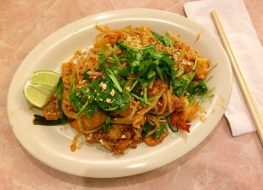 pad thai topped with cilantro and served with lime wedge
