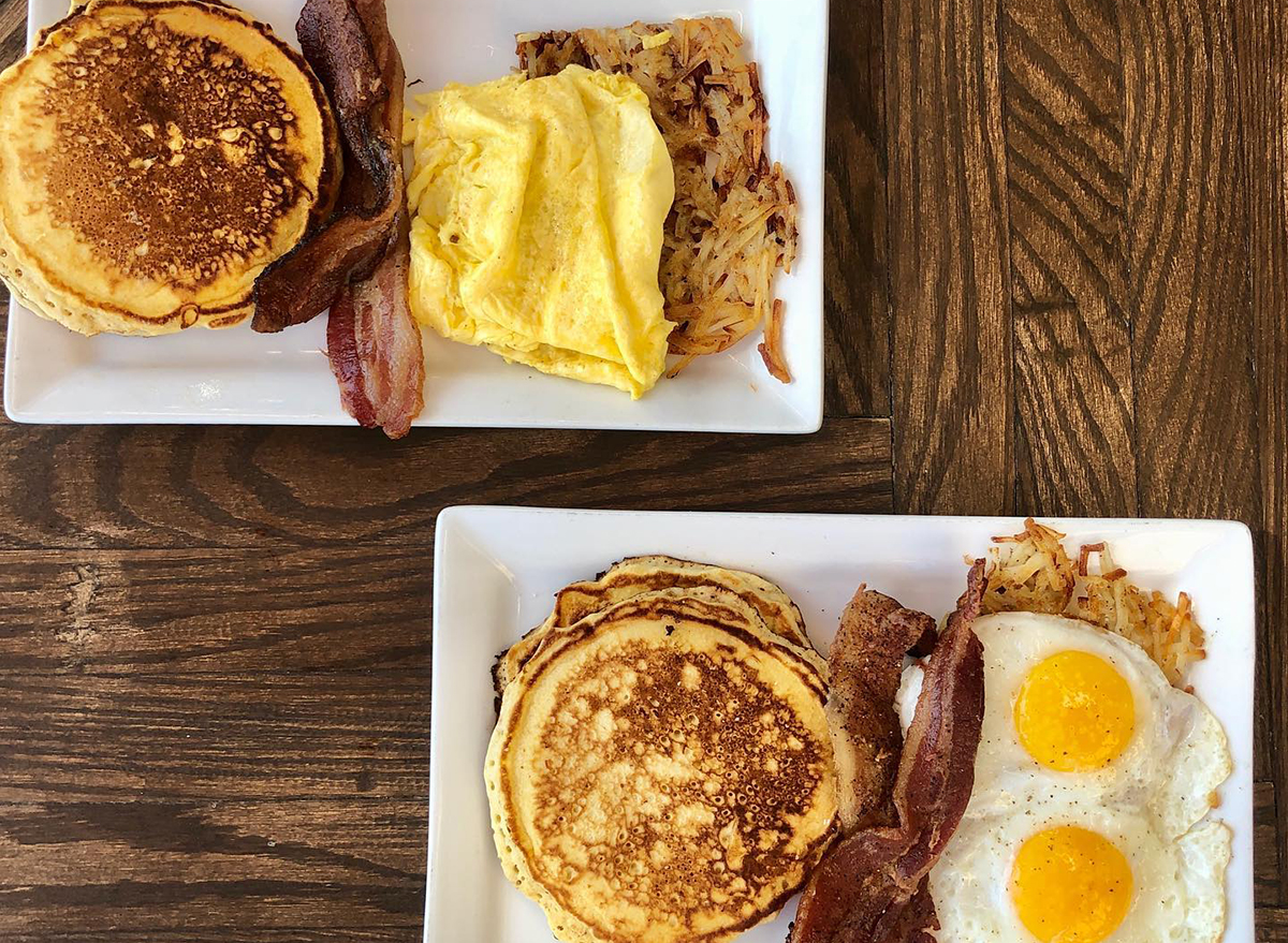 two plates of pancakes with eggs and bacon
