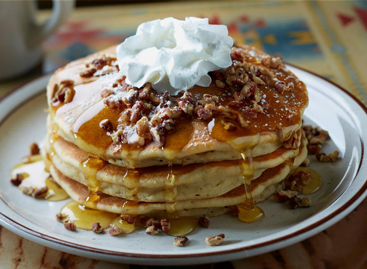 stack of pancakes with nuts and whipped cream
