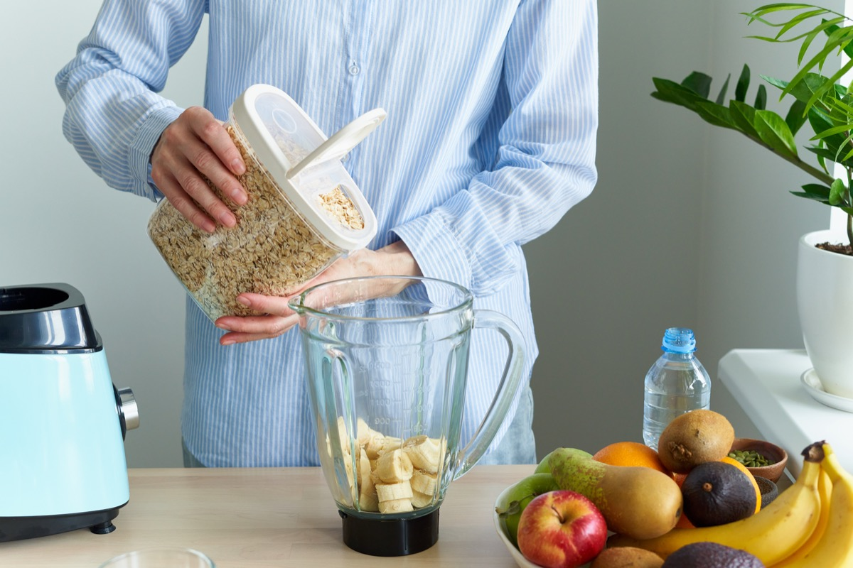 man pouring oatmeal into blender