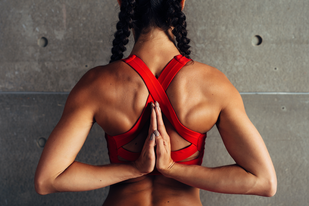 Close up fit woman with arms behind back doing stretching exercises.