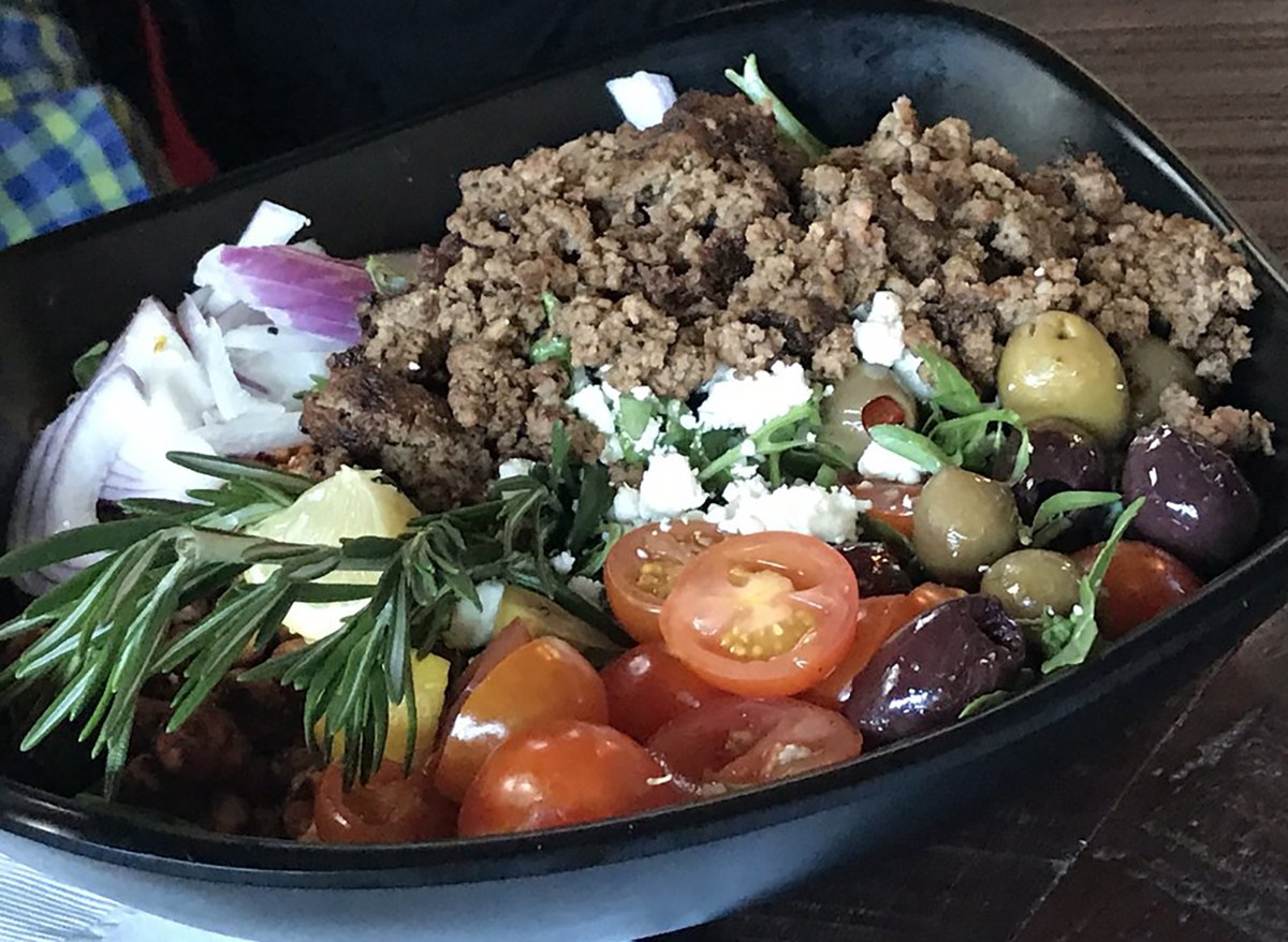 salad topped with rosemary sprigs tomatoes and ground beef