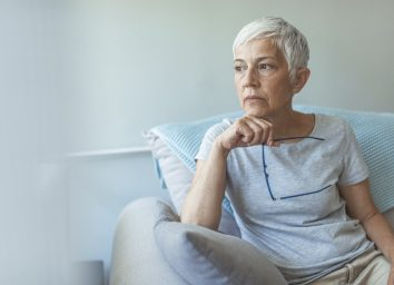 Senior woman looking through the window.