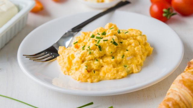scrambled eggs with chives on white plate