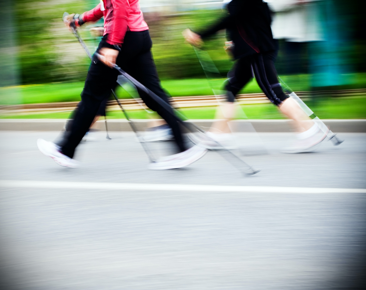 Woman nordic walking race on city streets. Walkers in marathon competition running fast