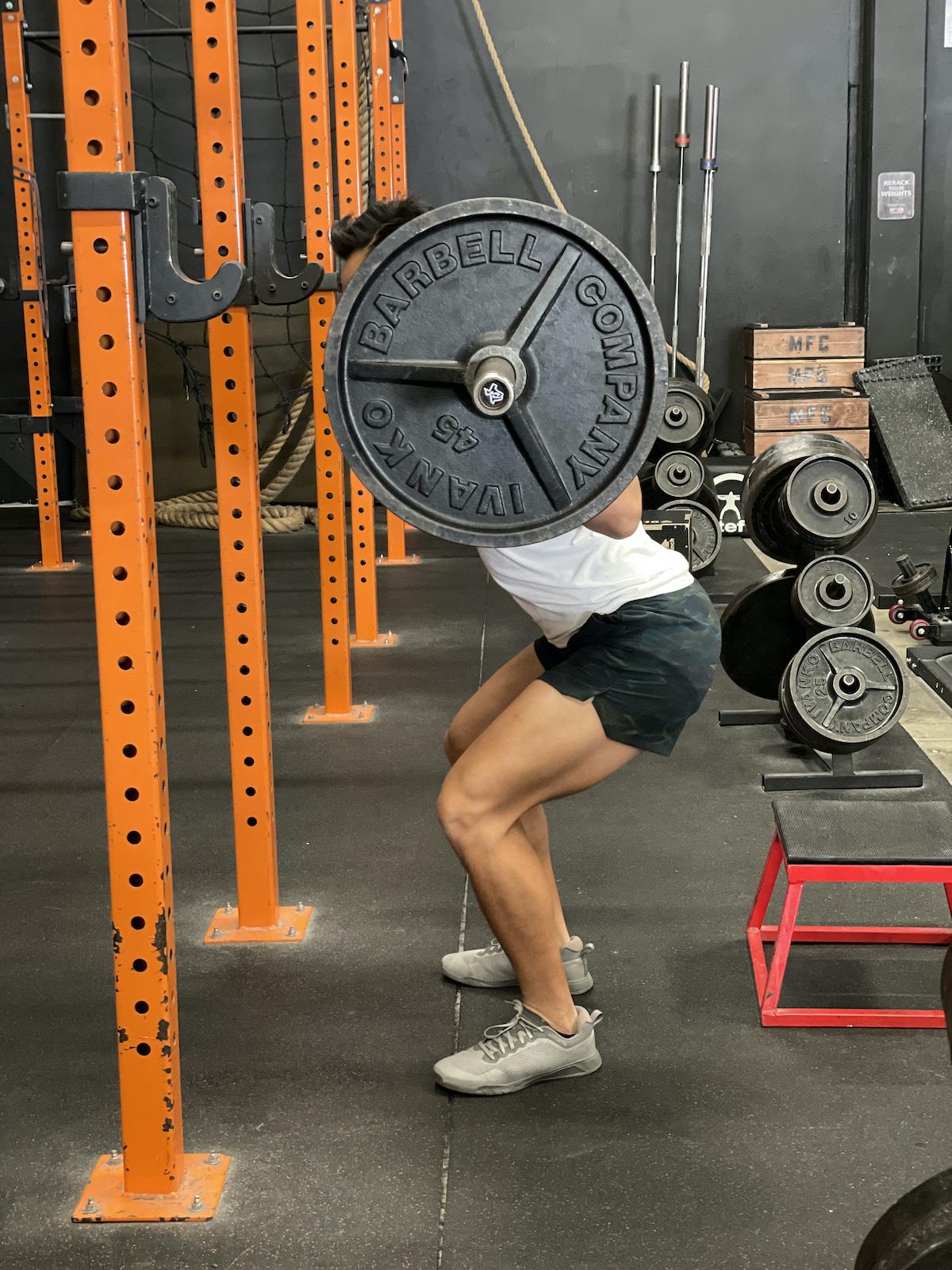 tim liu doing a squat with an extra quarter rep