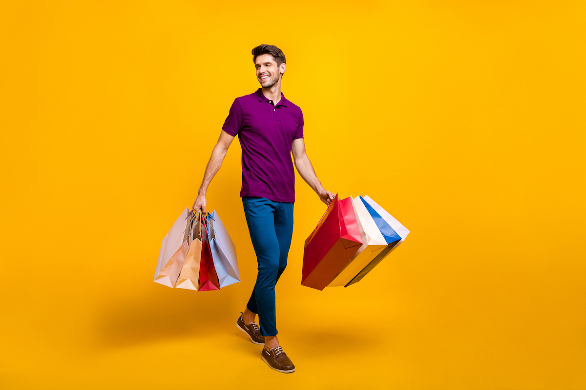 Full length body size view of his he nice attractive cheerful cheery glad content guy carrying new things colorful packages isolated over bright vivid shine vibrant yellow color background