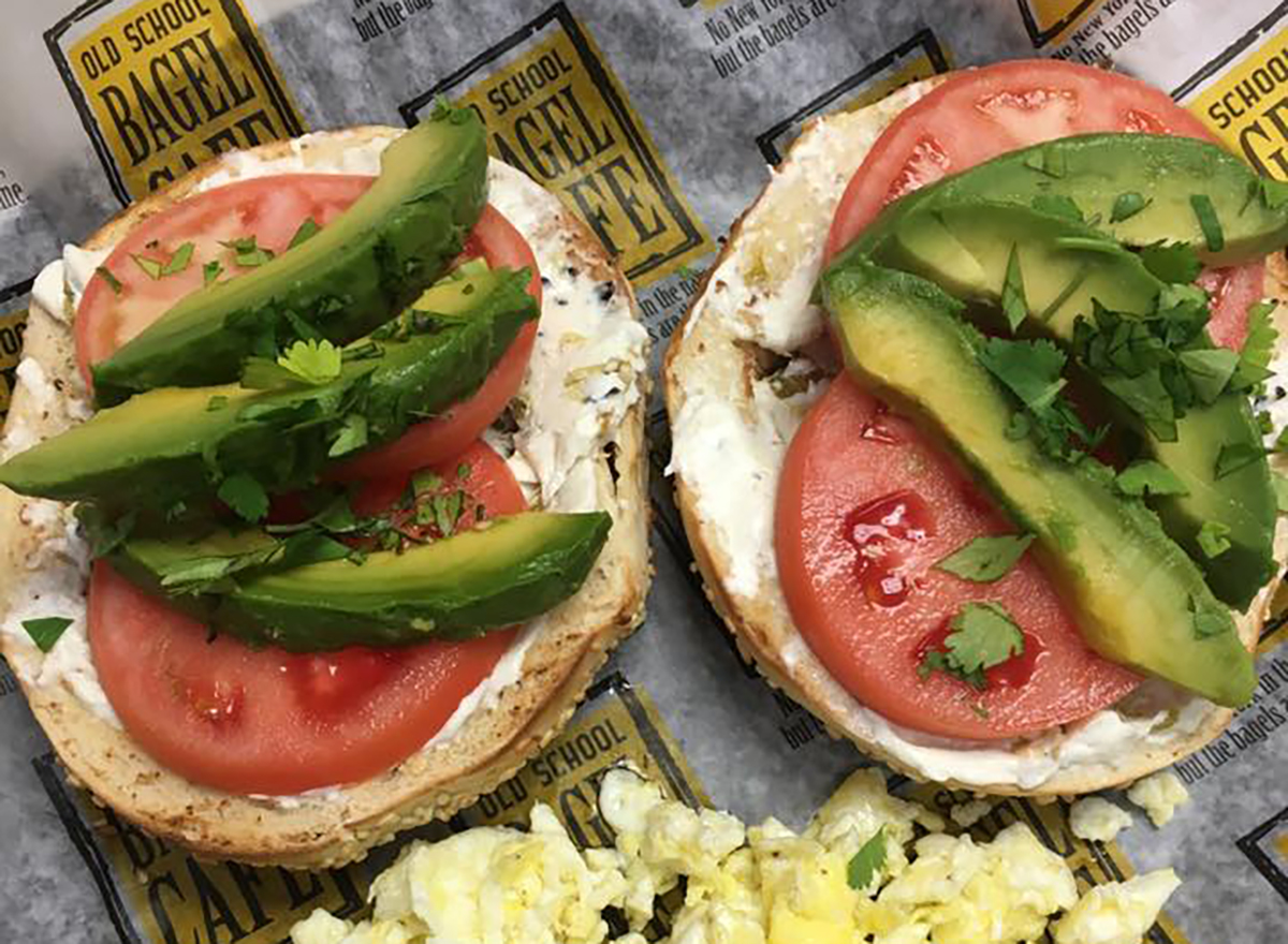 two bagel halves with tomato and avocado