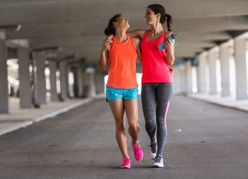 Couple of female friends jogging on the city street under the city road overpass.They relaxing after jogging and making fun.Embracing each other. Walkers