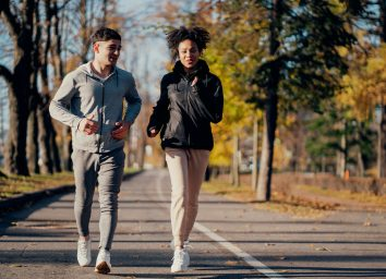 Sports couple in the park in the morning. They are engaged in long-distance running. Heart training cardio system in the fresh air, useful for blood vessels. Comfortable sportswear.