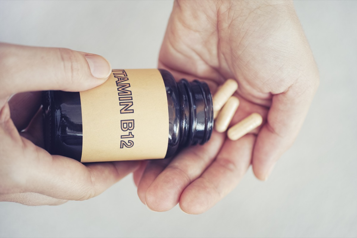 Person taking out Vitamin B12 pills out of bottle.