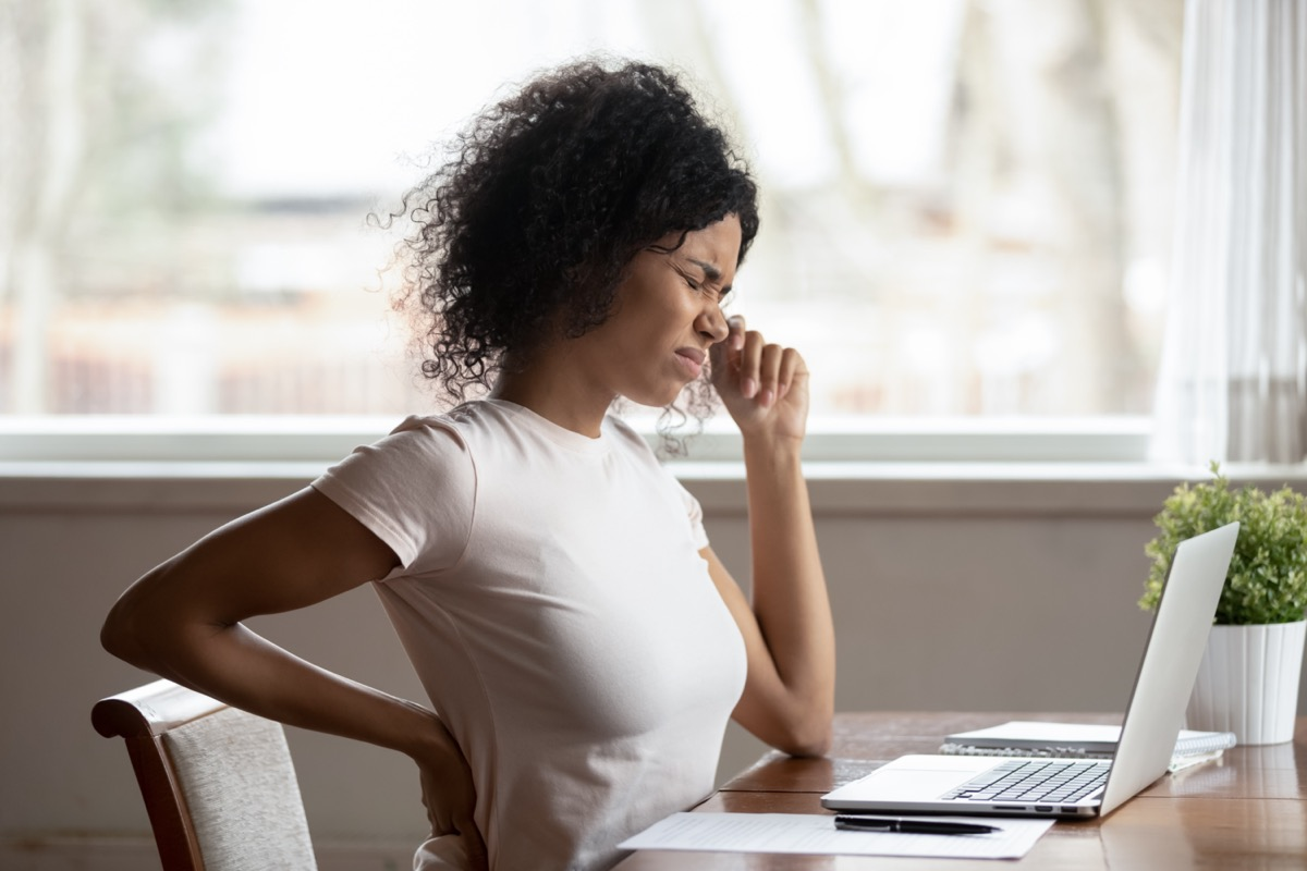 Female worker sit at desk touch back suffer from lower spinal spasm, hurt unhealthy biracial woman stretch have strong backache.