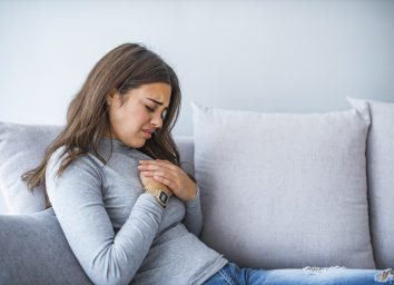 Woman holding hand to spot of pain area, chest