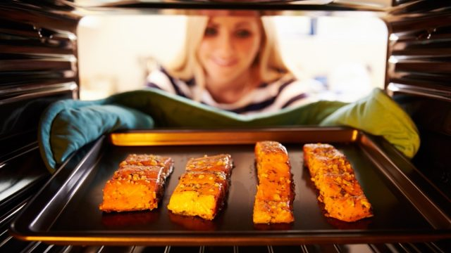woman removing baking sheet with salmon from oven