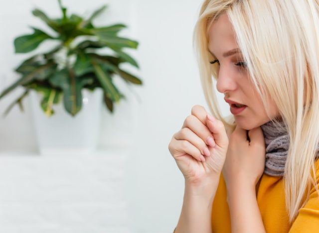 Blonde woman coughing.