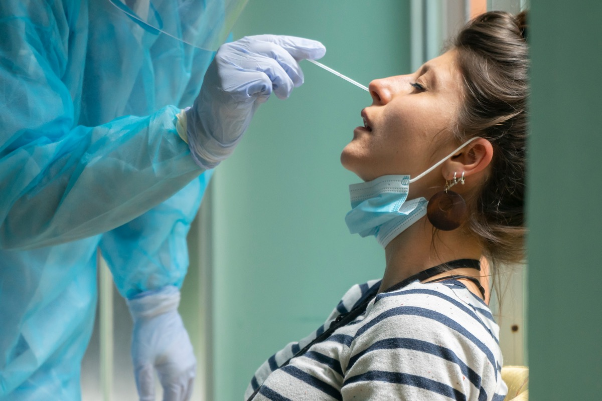 Healthcare worker with protective equipment performs coronavirus swab on a woman.