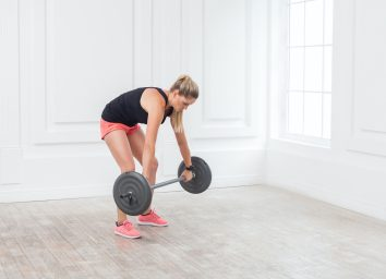 Side view portrait of young athletic beautiful bodybuilder woman in pink shorts and black top doing wrong squats and exercising at the gym with the barbell on white wall. indoor, studio shot,