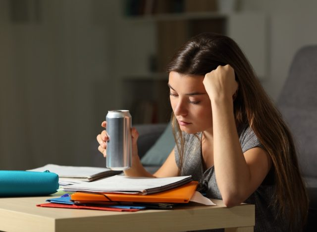 young woman drinking energy drink while studying