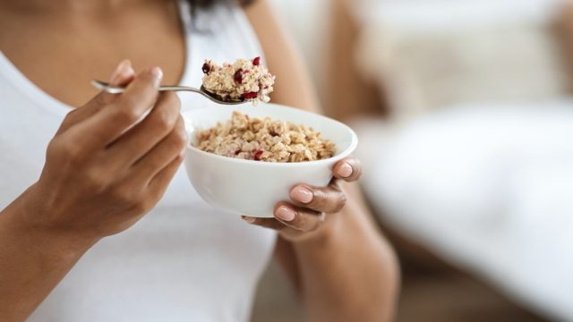 young woman eating oatmeal with cranberries out of a white bowl
