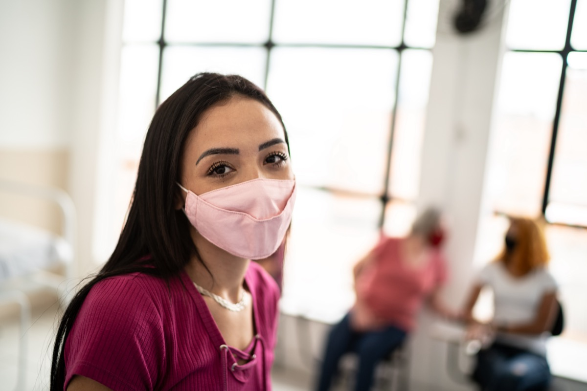 woman in a hospital waiting room - wearing face mask