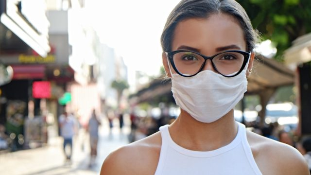 Woman wearing face mask on the busy street.