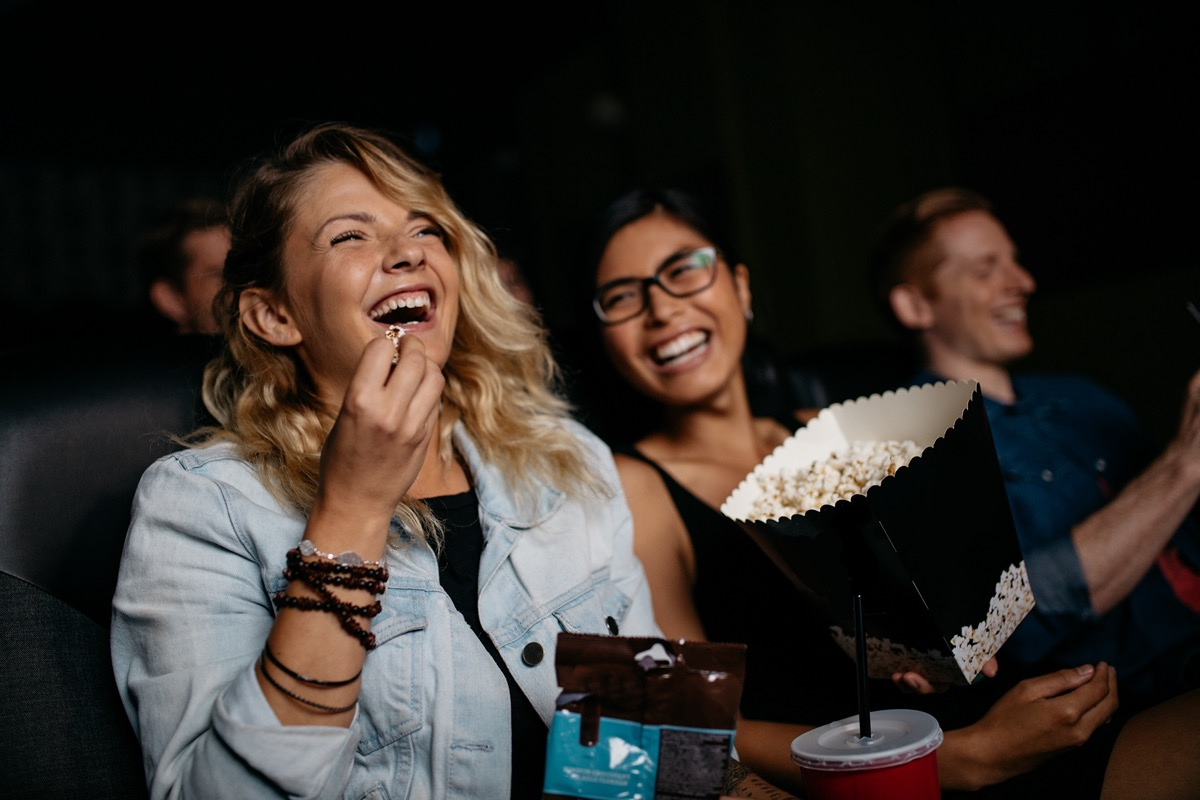 Woman with friends watching movie in cinema and laughing.