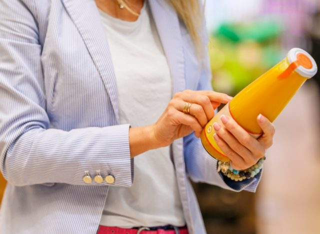 Woman reading ingredients and nutrition information on juice bottle's label.