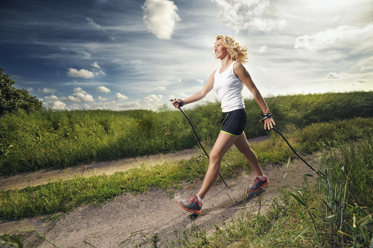 woman nordic walking outdoors with proper form