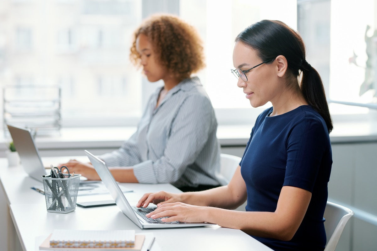 Two women sitting by desk in front of laptops.