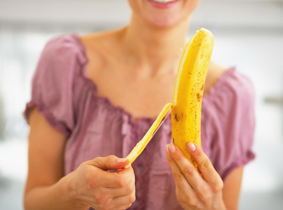 woman in pink shirt peeling banana