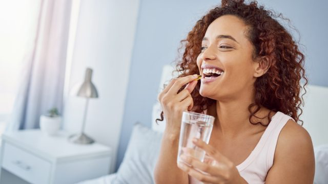 Woman taking her medication in her bedroom at home.