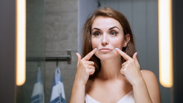 Young woman checking wrinkles on face in front of a bathroom mirror