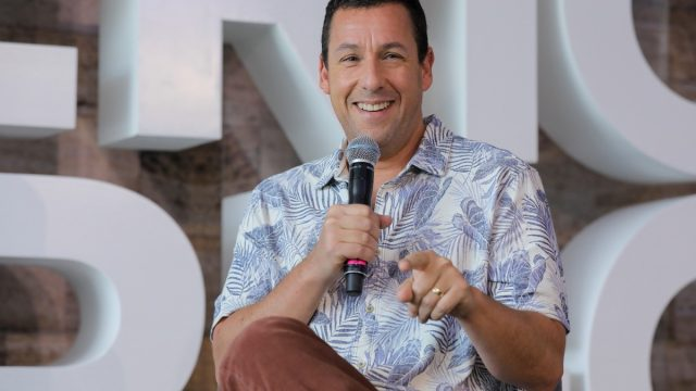 adam sandler holding microphone and laughing