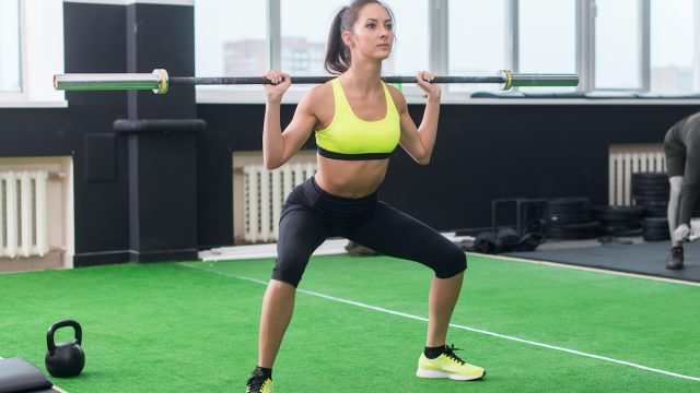young fit woman doing squats with barbell, exercising back and legs muscles