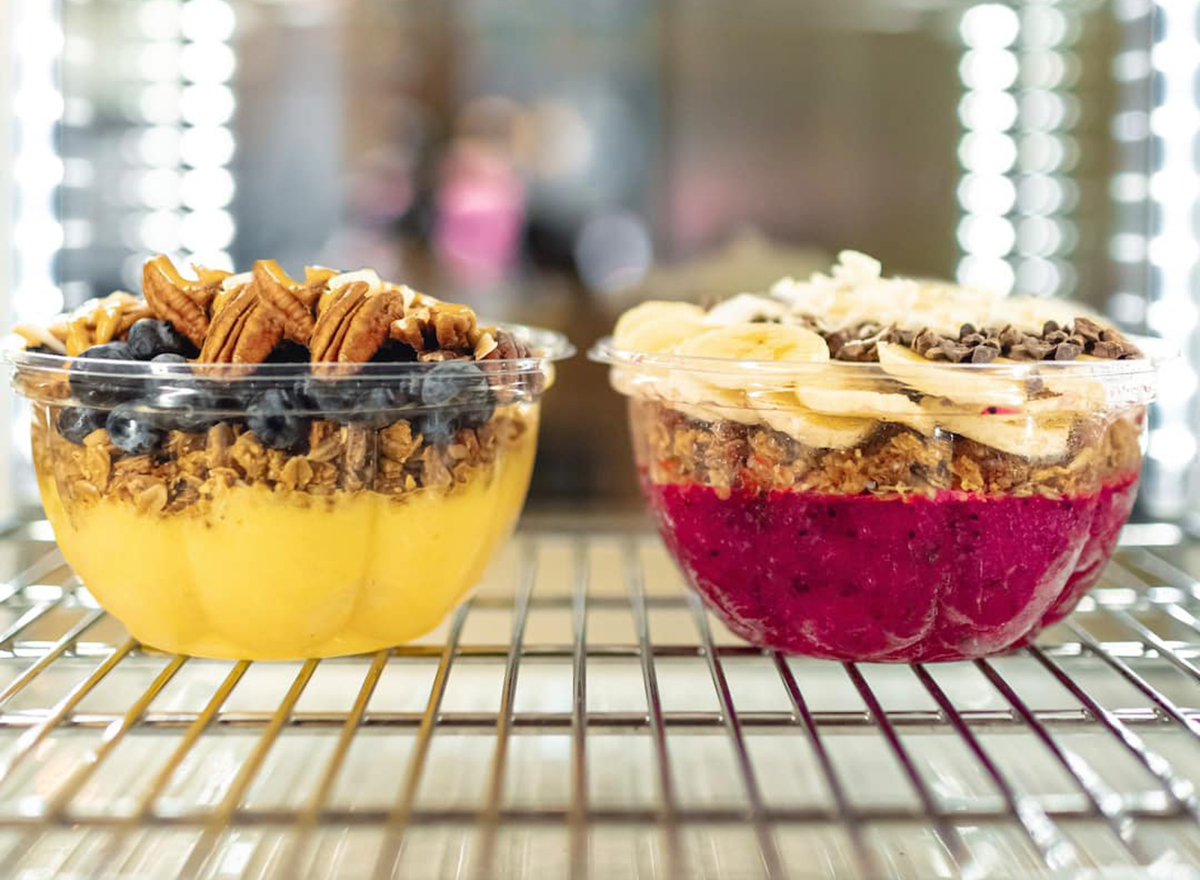 two smoothie bowls on a to-go rack