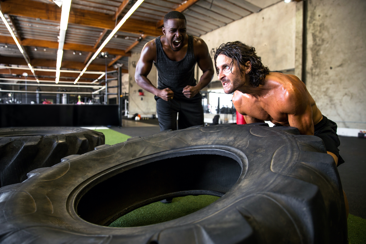 Workout partners scream and shout inspiring each other for motivation during intense extreme session