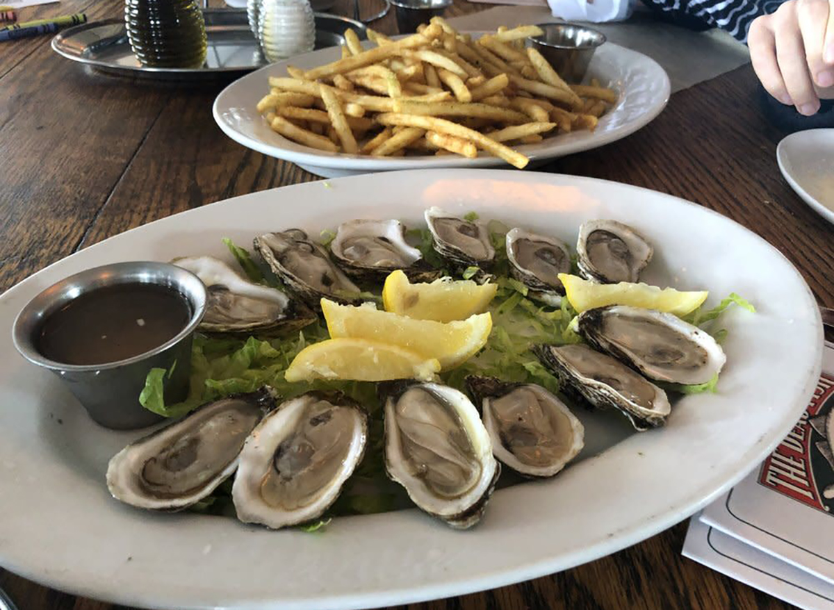 plate of raw oysters with lemon wedges