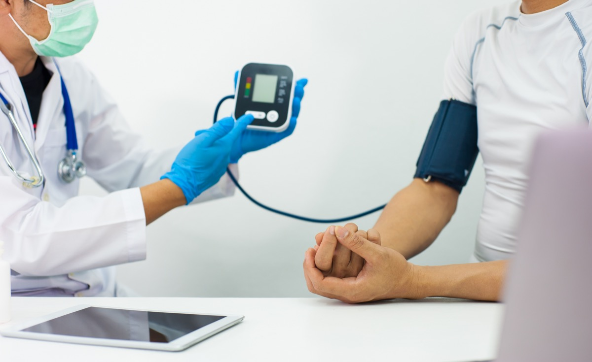 Doctor uses a sphygmomanometer to check the blood pressure of a patient.