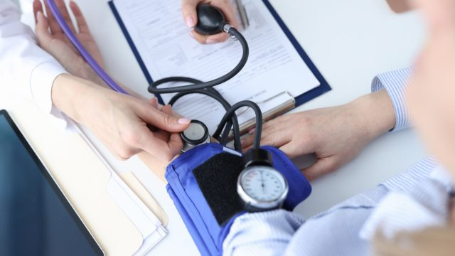 doctor measuring a patient's blood pressure with blood pressure cuff