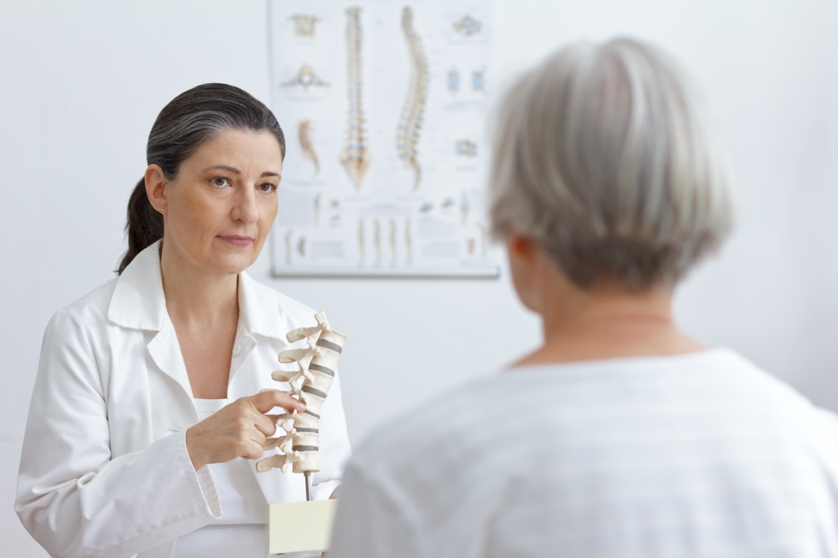 Orthopedics doctor showing senior patient a slipped disk on a backbone model.