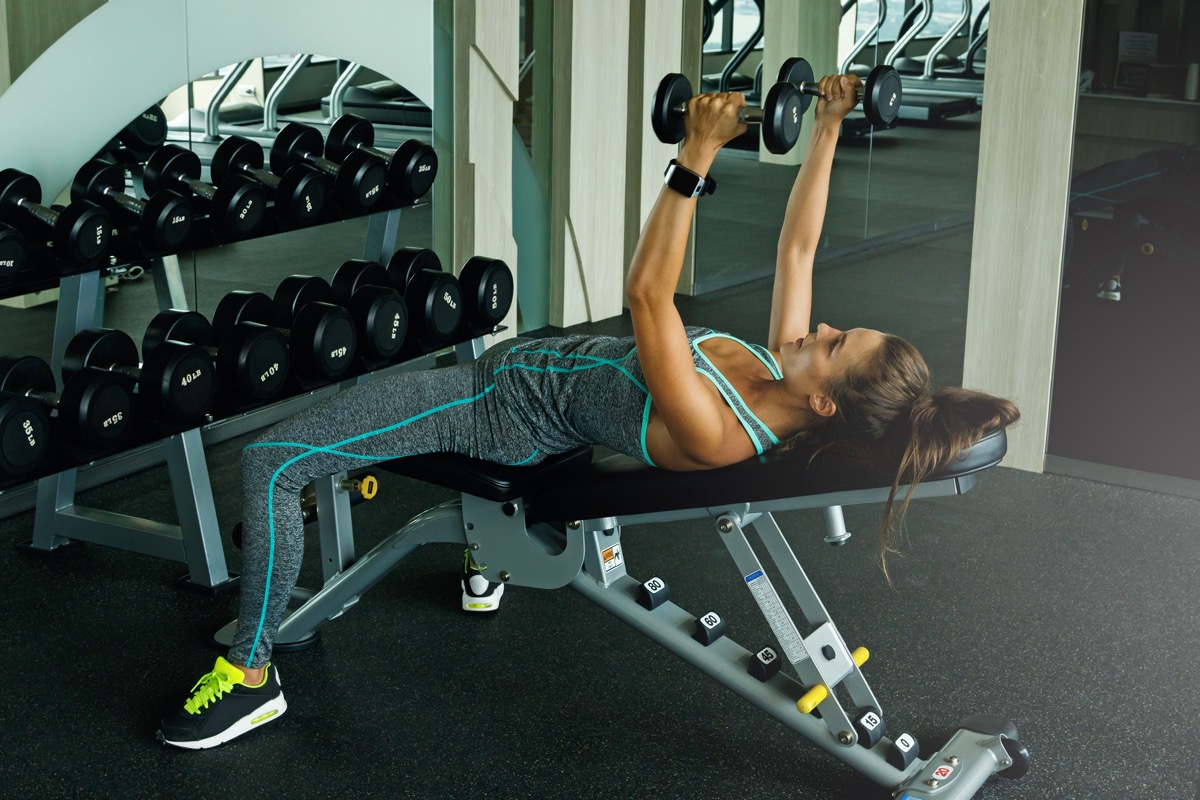woman working out with dumbbells in gym