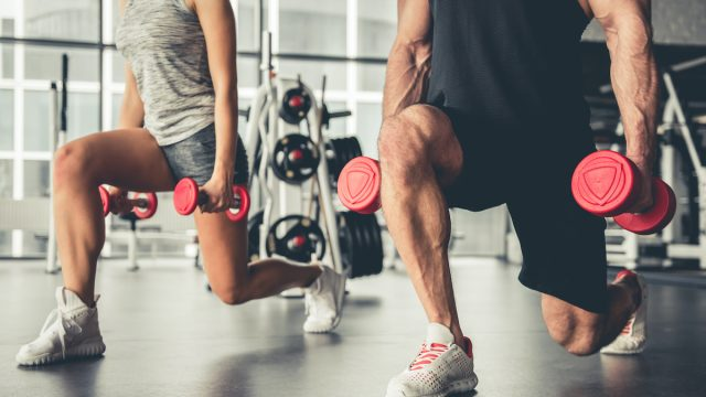 Attractive sports people are working out with dumbbells in gym
