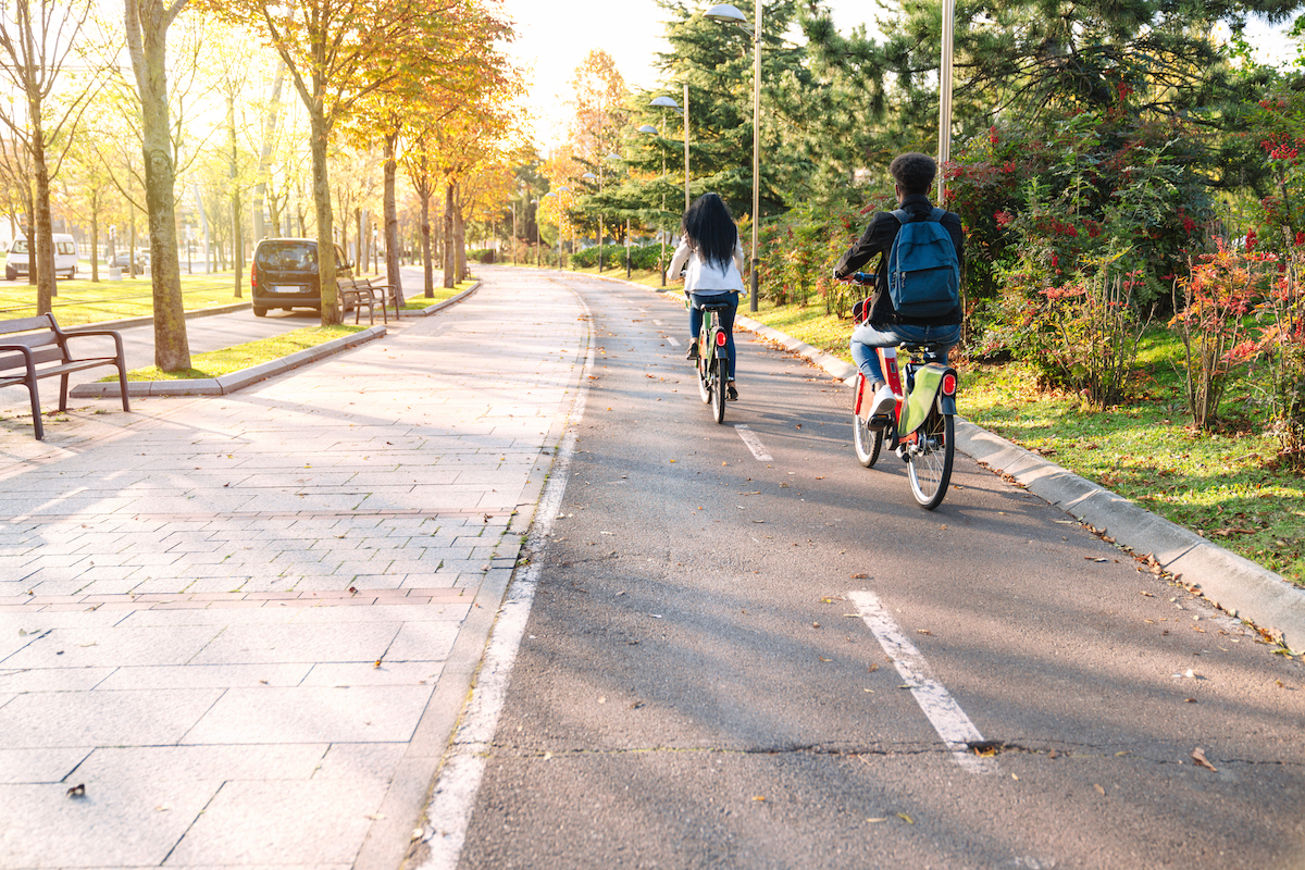 two teenagers young students man and woman riding along a bicycle path with a sharing electric bicycle e-bike in a beautiful park with many trees at sunset