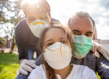 A girl taking a selfie of her family outdoors with face masks.
