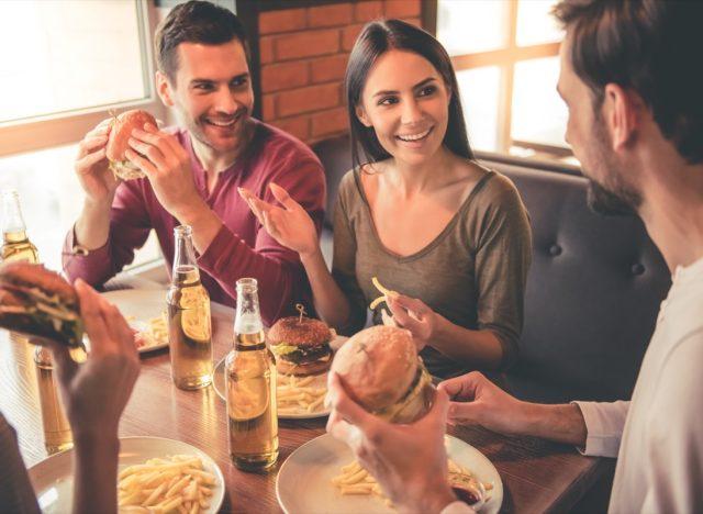 friends eating burgers in restaurant