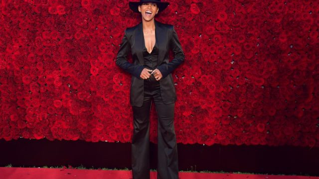 halle berry smiling in black suit and hat in front of rose wall