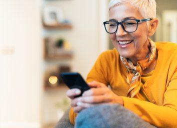 Modern mature woman texting at home