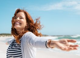 Happy mature woman with arms outstretched feeling the breeze at beach.
