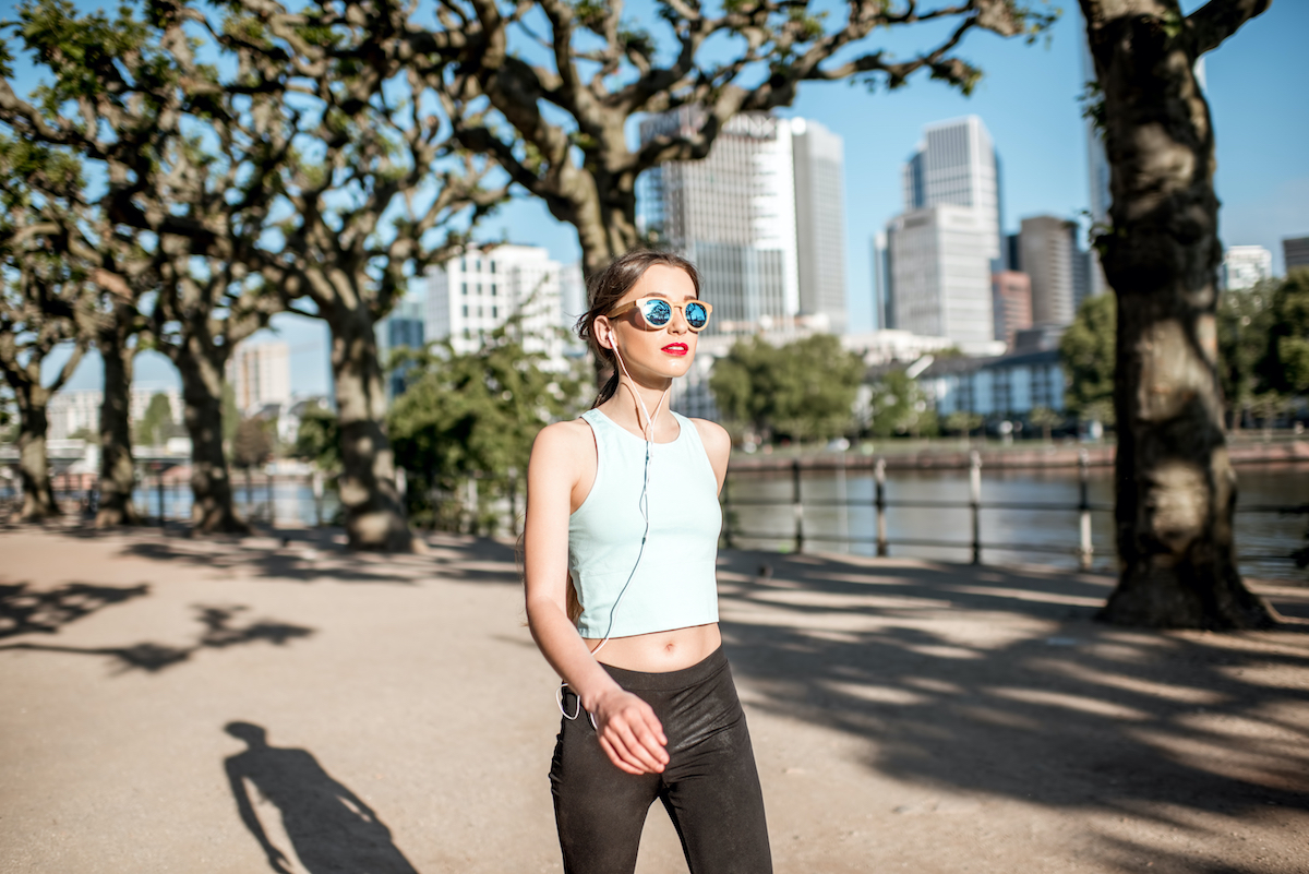 Young woman in sportswear having a morning exercise walking in the park with skyscrapers on the background in Frankfurt city